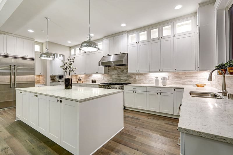 Gourmet Kitchen Features White Shaker Cabinets With Marble Countertops Stone Subway Tile Backsplash And Gorgeous Kitchen Island