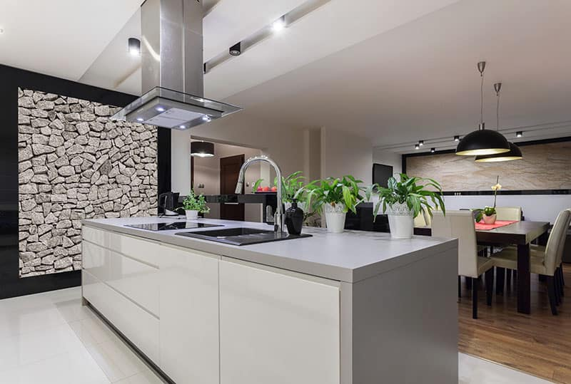 Large Brown Triangle Island In A Large Kitchen With Stone Wall