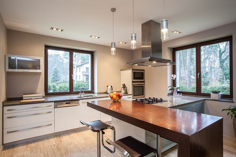Long Wooden Kitchen Island In A Travertine House Horizontal View Of Kitchen