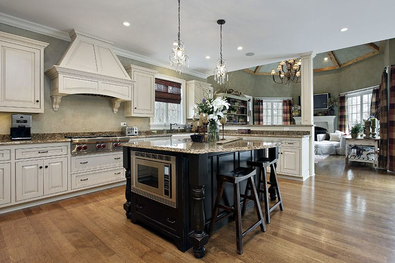 Marble Countertop Island With Black Wooden Cabinetry In An Open Ended Luxurious Kitchen