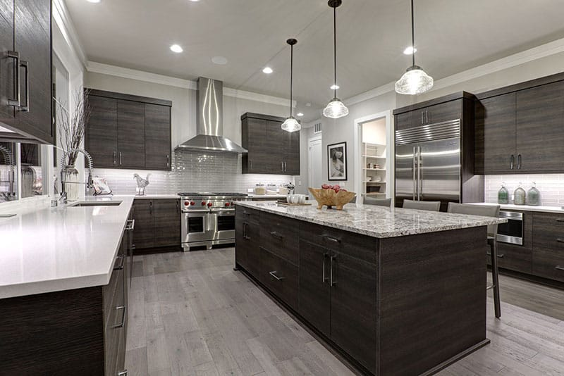 Modern Gray Kitchen Features An Island With Dark Gray Flat Front Cabinets Paired With White Quartz Countertops And A Glossy Gray Linear Tile Backsplash
