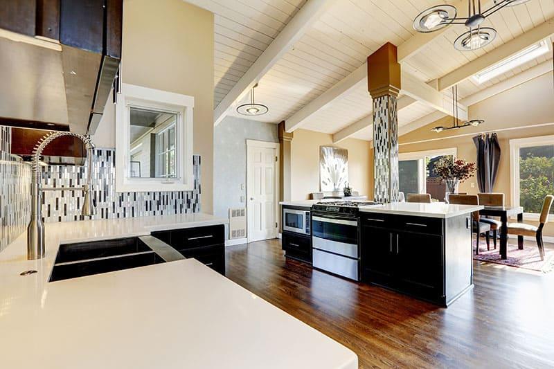 Modern Kitchen With Dark Brown Cabinets Steel Appliances And Kitchen Island With Bar Stools