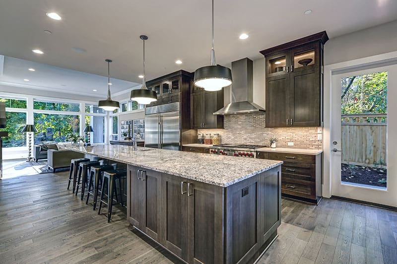 Oversized Kitchen Island In A Modern Kitchen With Bar Stools Granite Countertops Huge Refrigerator And Beige Backsplash