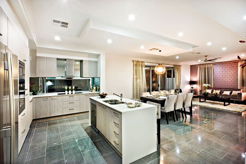 Pure White Island In A Modern And Shiny Kitchen With Dining And Living Area On The Reflective Tiles