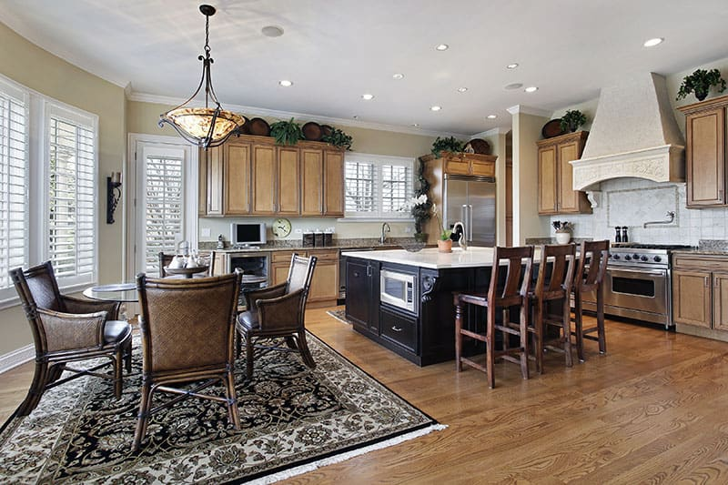Dark Wood Island In A Spacious Kitchen With Plenty Of Chairs