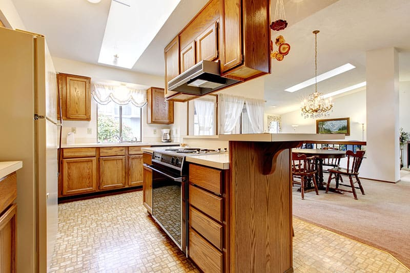 Full Of Life Kitchen Island In Bright Kitchen Room With High Vaulted Ceiling And Skylights
