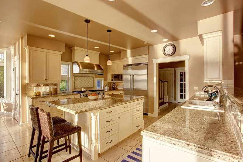 Island With Beige Countertops And White Cabinets In A Luxurious Kitchen