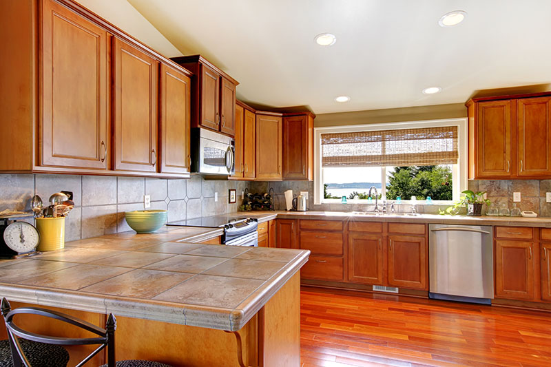 Dark Stained Hardwood Floor Contrasting The Ceiling While Maintaining A Surprising Consistency With The Cabinets And Wall Finish