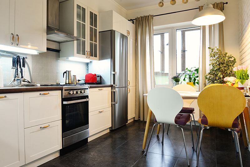 Dark Stone Floor Creates A Dark Shade And Blends In With The Cooker And Refrigerator