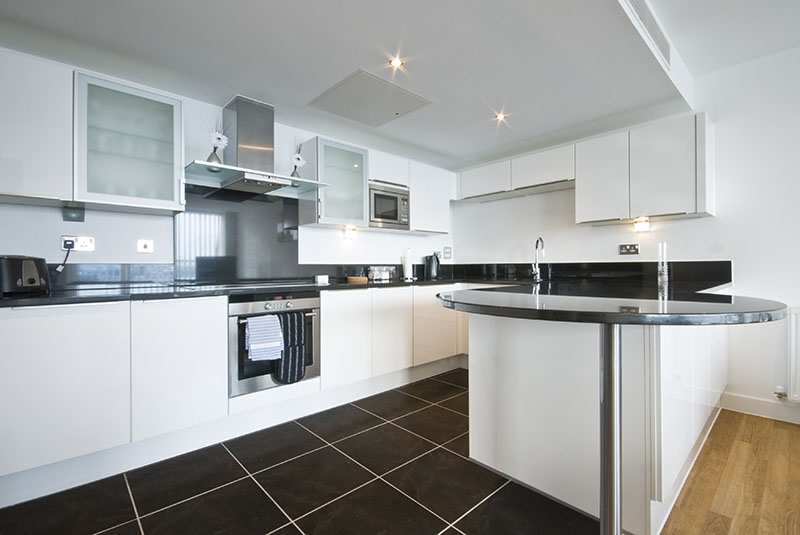 Dark Tile Floor Complements The Black Accent Delivered Through The Countertops In The Kitchen
