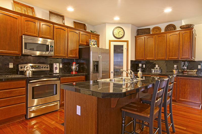 Kitchen Magnified By Dark Golden Cherry Cabinets And A Matching Hardwood Floor